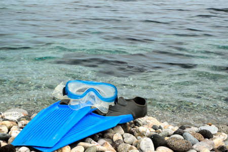 Flippers and snorkel mask on the pebbles beach