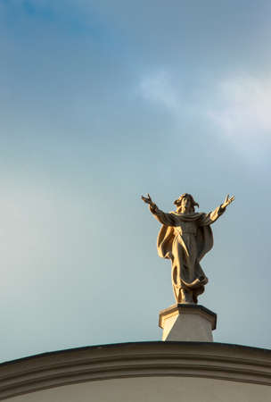 Angel on the roof of the church with the hands pointing to the sky Stock Photo