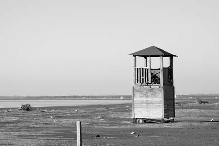 swiming: Old tower for lifeguards on the deserted beach in black and white