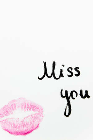 Miss you text with lipstick kiss on white background