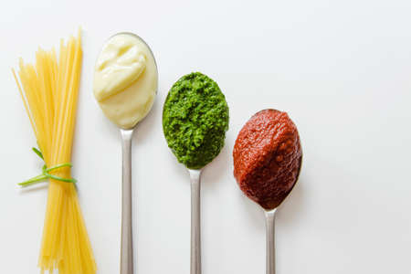 Spaghetti and three spoons with different condiments - tomato sauce, mayonnaise and pesto Stock Photo