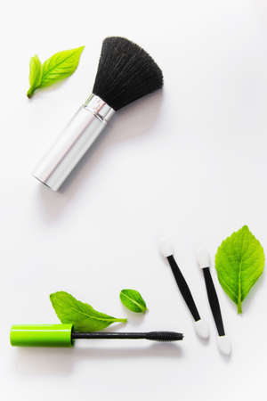 Top view of a mascara and brushes on white background with green leaves