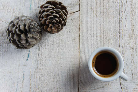 Top view of coffee cup with pine cones on white wooden background. Cold weather - hot coffee concept