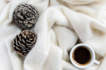 A cup of coffee in a cozy warm blanket with pine cones. Autumn-winter concept