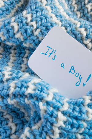 Its a boy baby shower, announcement card on cozy woolen blanket and space for text. New arrival in the family