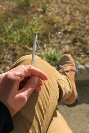 Adult person with a cigarette in hand, personal point of view Stock Photo