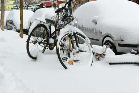 Parked cars and bikes covered by the snow, space for text