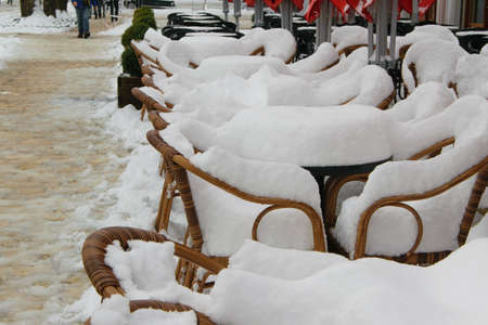 Tables and chairs of cafe bar, covered with snow