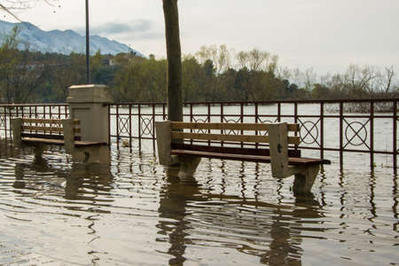 Raised water level from the river arrives on the sidewalk, concept - bad weather conditions