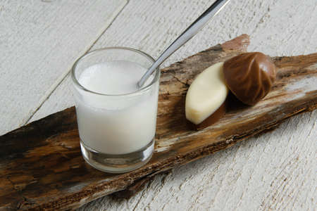 Top view of minimal milk drink style. Milk glass cup and chocolates on table, space for text