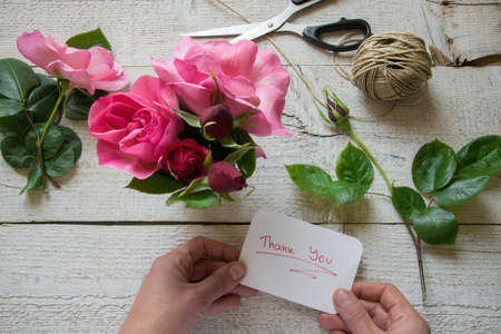 Top view of female decorator holding Thank you card, arranging roses on the wooden table, Concepts - fiorist, occupation, hobby, small business