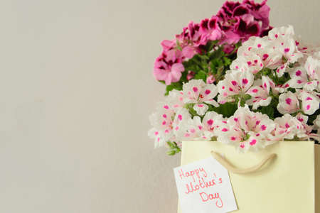 Paper bag with fresh flowers and greeting card for the Mothers day on the wooden table, space for text Stock Photo