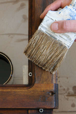Top view of woman hand brush with colored lacquer wooden table indoors. Repair, DIY concept