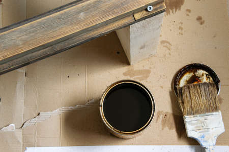 Top view of brush, colored lacquer and wooden table indoors. Repair, DIY concept