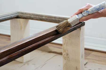 Woman brush with colored lacquer wooden table indoors. Repair, DIY concept Stockfoto