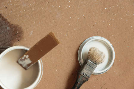 Top view of brush and white tin color on carton, indoors. Repair, DIY concept