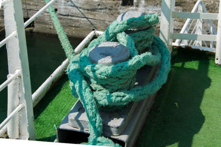 Metal rusting bollard with heavy green ropes on a ship Imagens