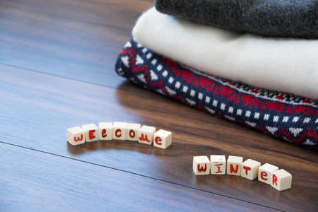 Crop view of woolen sweaters with Welcome Winter text, fashion seasonal concept