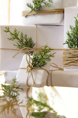 Elegant white handcraft gift boxes and fresh fir branches, seasonal celebration and eco-friendly concept 스톡 콘텐츠