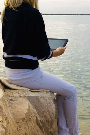 Crop view of attractive young woman  working with digital tablet sitting at seaside cliff edge. Freelance work, traveler concept, space for text Stock fotó