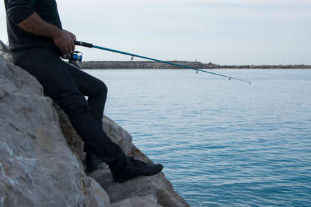 Fisherman holds an angling rod, sport outdoor activity concept 版權商用圖片