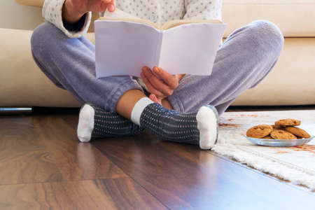 Cropped view of woman with pajamas sitting on the wooden floor at home with hot drink and cookies, reading a book- Everyday cozy life concept Reklamní fotografie