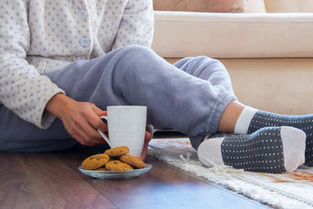 Cropped view of woman with pajamas sitting on the wooden floor at home with hot drink and cookies. Everyday cozy life concept
