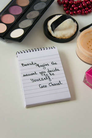 Coco Chanel quotes written on a block note, pearl accessories and make up on white background, inspiration phrase