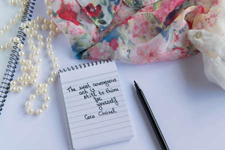 Coco Chanel quotes written on a block note, pearl accessories and  and silky flower shirt ,inspiration phrase