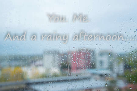 Rain drops on window and romantic text on You.Me. And a rainy afternoon Tender amorous concept in bad weather days