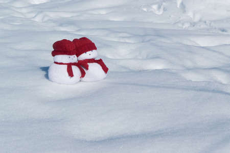 Two lovely snowmen toys on the white snow, holiday celebration concept Banco de Imagens