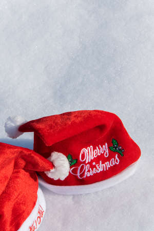 Two Christmas red hats on the white snow, holiday celebration concept Reklamní fotografie