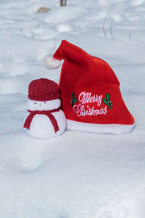 Christmas red hat and a lovely snowmen toy on the white snow, holiday celebration concept