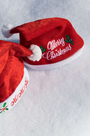 Two Christmas red hats on the white snow, holiday celebration concept Banco de Imagens