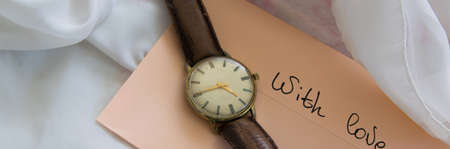 Pastel color envelope with antique wristwatch on a silky cloth, romantic love concept Standard-Bild - 120523931