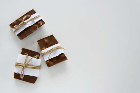 Top view of broken chocolate pieces wrapped in white paper and rustic twine on the white background