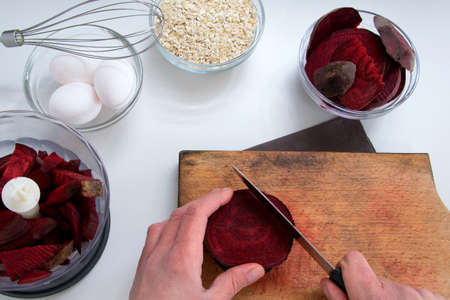 Top view of woman hands cooking healthy dessert with red beet roots, oats and fresh eggs Imagens