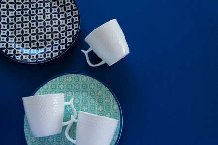 Overhead flat lay view of different clean tableware on blue background