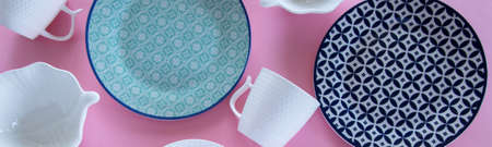 Overhead flat lay view of different clean tableware on pink background Archivio Fotografico