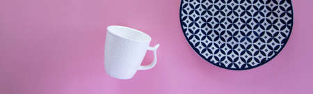 Overhead flat lay view of clean tableware (blue plate and  white coffee cup) on pink background