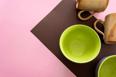 Overhead flat lay view of different clean ceramic tableware on pastel color background Archivio Fotografico