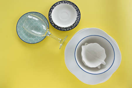 Different porcelain tableware on fresh yellow background