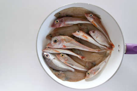 Top view of mixed sea fishes in a pan ready to be cooked Stock Photo