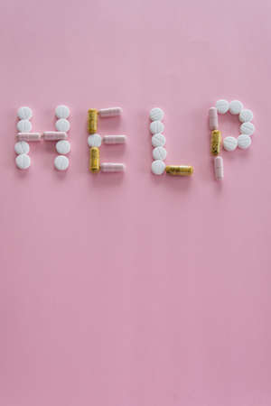 Different medication pills in HELP word shape on pink background. Healthcare, medical concept. Addiction Imagens