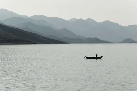 Silhouette di un pescatore in piccola barca nel lago, Albania