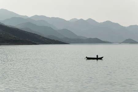Sylwetka rybaka w małej łódce na jeziorze, Albania