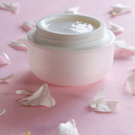 Organic skin care product and delicate flower petals on pink background. Healthy cosmetic products . Wellness beauty treatment. Banque d'images