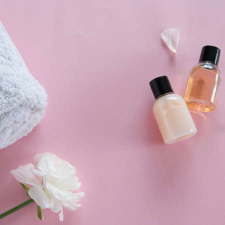 Top view of cosmetic products and delicate flowers on pink background. Wellness beauty treatment. Organic skin care products