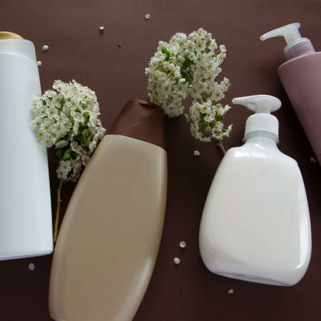 Top view of different hygienic products and flowers on brown background. Wellness beauty treatment. Organic health care products
