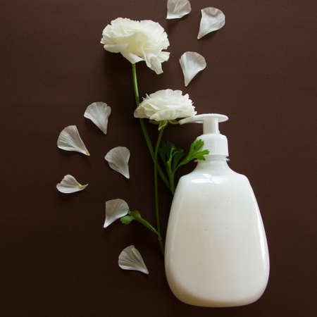 Top view of hygieniccosmetic product and flowers on brown background. Wellness beauty treatment. Organic health care products